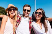 image of road trip  - Three young happy people looking at camera and smiling while enjoying road trip in convertible - JPG