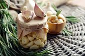 Canned garlic in glass jar and rosemary branches, on wicker mat background