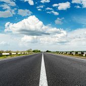 asphalt road with white line and blue sky with clouds over it