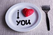 Cookie in form of heart on plate with inscription I Love You, on napkin background