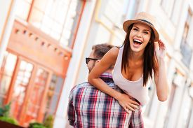 stock photo of bonding  - Rear view of young cheerful man carrying his beautiful girlfriend on shoulder while walking by the street - JPG