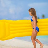 stock photo of mattress  - Adorable girl with inflatable air mattress on white beach - JPG