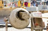 picture of throw up  - Close up of shovel throwing cement into concrete mixer on construction site - JPG