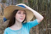 stock photo of windy  - Freckled happy girl in hat in windy weather - JPG