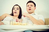 stock photo of horror  - Frightened young attractive couple sitting on the couch in living room at home covered with blanket and watch scary horror on television with popcorn - JPG