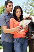 foto of hispanic  - Worried Hispanic Couple Checking Mailbox - JPG