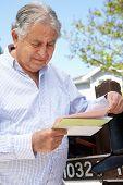 stock photo of mailbox  - Worried Senior Hispanic Man Checking Mailbox - JPG