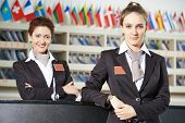 picture of receptionist  - Happy female receptionist worker standing at hotel counter - JPG