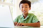 stock photo of pre-teen boy  - Young Asian boy using laptop - JPG