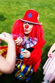picture of clowns  - Clown woman blowing soap bubbles outdoor birthday celebration - JPG