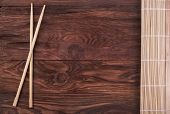 image of chopsticks  - Chopsticks and folded bamboo napkin on a wooden background - JPG