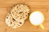 image of shortbread  - Two shortbreads rings with peanuts and cup of milk on wooden bamboo table top view - JPG