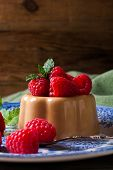 picture of dessert plate  - Italian dessert coffee panna cotta served on a blue plate with raspberries and fresh mint on vintage wooden bckground - JPG
