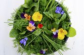 pic of edible  - Cooking with herbs concept with fresh herbs and edible flowers in modern yellow fry pan skillet on white wood table - JPG