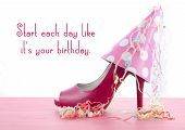 picture of stiletto heels  - Pink high heel shoe on pink wood shabby chic table with Start Each Day Like Your Birthday quote - JPG