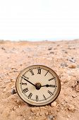 stock photo of analog clock  - Classic Analog Clock In The Sand On The Rock Desert