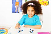 stock photo of numbers counting  - Cute African girl puts blue coins as values on numbers  learning to count during developmental game at the desk while sitting in playroom with drawings - JPG