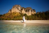 picture of barefoot  - bride and groom barefoot at edge of transparent water against cliffs and tropical trees - JPG