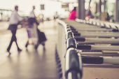 stock photo of trolley  - Close up trolleys luggage with blurred of passenger in airport retro filter effect - JPG