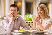 image of boredom  - Man is getting bored in restaurant while his woman looking at phone - JPG
