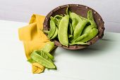 image of snow peas  - Snow peas on wooden bowl with green napkin on wooden table - JPG