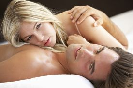 picture of laying-in-bed  - Young Couple Relaxing On Bed - JPG