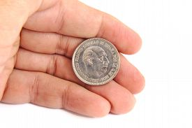 stock photo of spanish money  - Caucasian man hand holding an old Spanish coin of 50 pesetas showing Franco dictator face on a white background - JPG