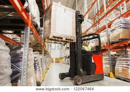wholesale, logistic, loading, shipment and people concept - man or loader on forklift loading cargo