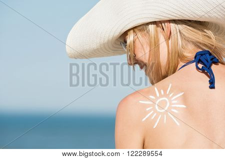 Close up of shoulder of beautiful woman with a sun drawn with the suntan lotion. Back pose of girl w