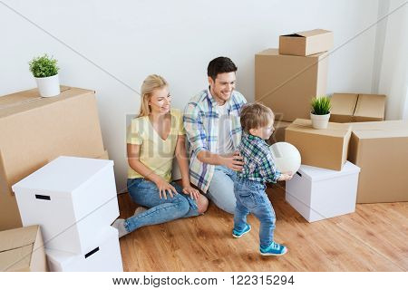 mortgage, people, housing, moving and real estate concept - happy family with boxes playing ball at