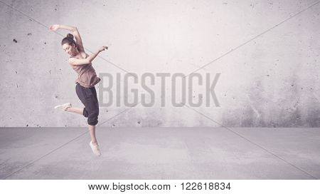A beautiful young hip hop dancer dancing contemporary urban street dance in empty clear grey wall ba