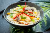 Bowls of Asian noodle soup with chicken,mushrooms, sweetcorn  and chili