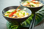 Bowls of Asian noodle soup with chicken,mushrooms, sweetcorn  and chilli