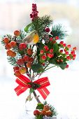 Christmas arrangement of ornamental apples(malus),fir branch and holly in vase
