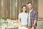 Happy young affectionate couple going to prepare or have breakfast in the kitchen poster