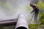 stock photo of sandblasting  - A worker sandblasting the weld during the construction of pipelines - JPG