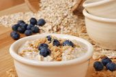 Hot delicious oatmeal and fresh blueberries sprinkled with brown sugar.  Uncooked oats in soft focus in background.  Macro with extremely shallow dof.