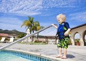 Little Boy Cautiously Stepping into Outdoor Pool in San Diego, California