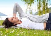 joven mujer acostada en una pradera frente a un lago