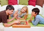 pic of boardgame  - a young father is playing chess with his children - JPG