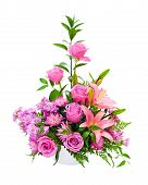 Colorful purple flower arrangement centerpiece with roses, lily, carnations, isolated on white.