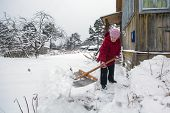 Elderly woman cleans the snow near home. poster