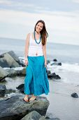 Beautiful Smiling Woman Stands Against The Ocean