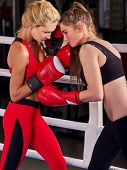 Two boxing women workout in fitness class. Sport exercise two female people. Boxer wearing red glove poster