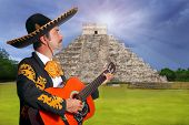 Charro Mariachi playing guitar in Chichen Itza pyramid Mexico