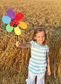 Little girl in whet field at harvest time playing with windmill toy