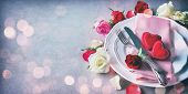 Valentines day table setting with plate, roses, red ribbon and hearts. Holidays background. Valentin poster