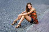 Beautiful Girl Sits On City Streets