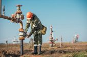 Oil Worker Is Turning Valve On The Oil Pipeline, Oil Deposit On The Background. poster