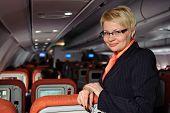 Posing stewardess near armchairs in the plane